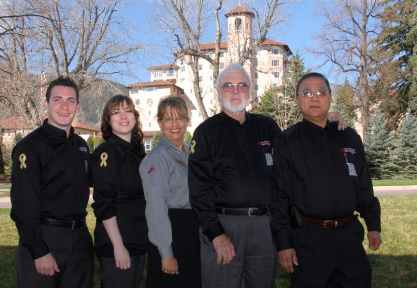 five people wearing grey and black standing, green trees in the background, beige and red building in the middle