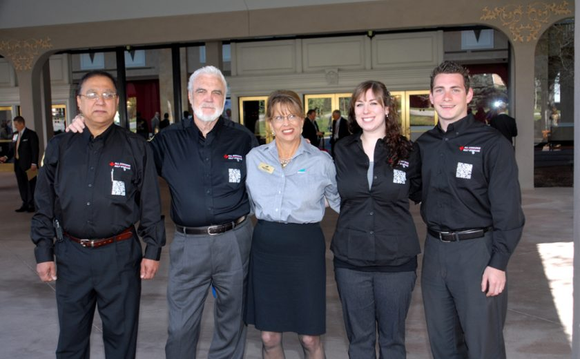 three men and one woman wearing all black dress shirts and pants, one woman wearing blue shirt and black skirt