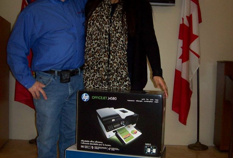 man wearing blue shirt and blue jeans next to woman wearing leopard print shirt and black sweater, black tv hanging on wall, red and white Canadian Flag, black and blue boxes in the front