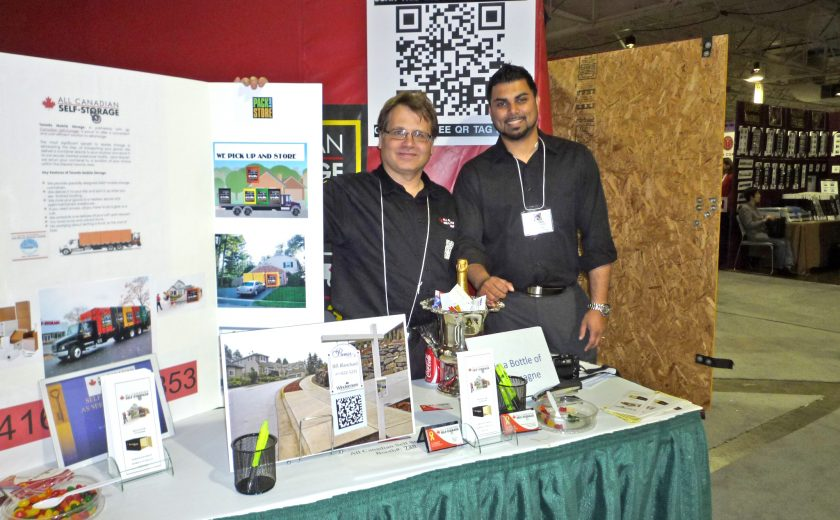 two men wearing black standing at booth, white and red boards, white table with green cloth