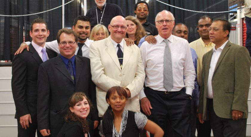 The All Canadian Self Storage Team, group of over 10 people standing, black curtain background