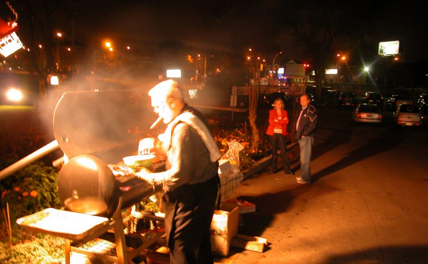 night sky, man barbecuing while holding a bowl, dark filled parking lot