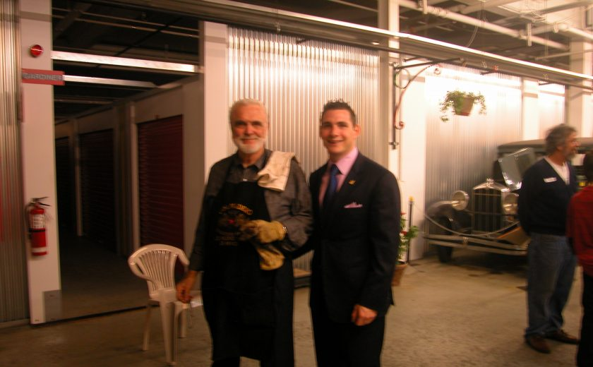 two men standing inside white and grey storage facility, one man wearing black apron, other man wearing black suit and pink dress shirt