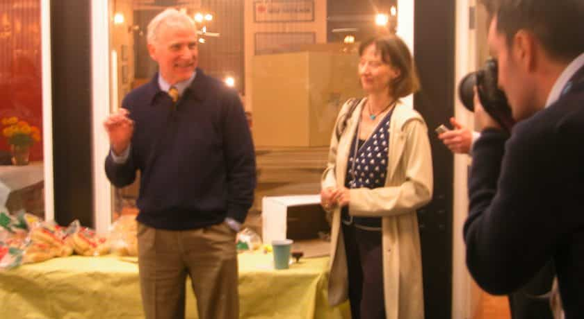 man smiling wearing a dark blue sweater and brown pants, standing in front of table with a yellow table cloth, woman standing with short hair wearing a blue and white polka dot shirt and long beige jacket, man taking picture of man and woman