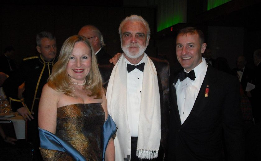 Garrison Officer's Ball, green lighting, two men wearing black and white suits, women wearing gold and blue dress