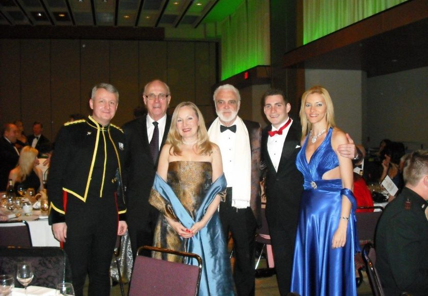 Garrison Ball, four men wearing suits and two women wearing gold and blue dresses