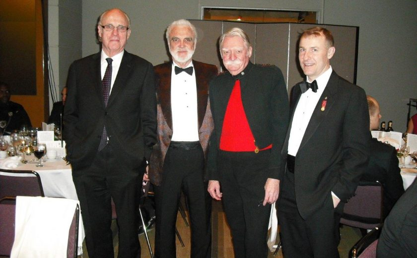 Garrison Officer's Ball, four men wearing suits, purple chairs and white tables in the background