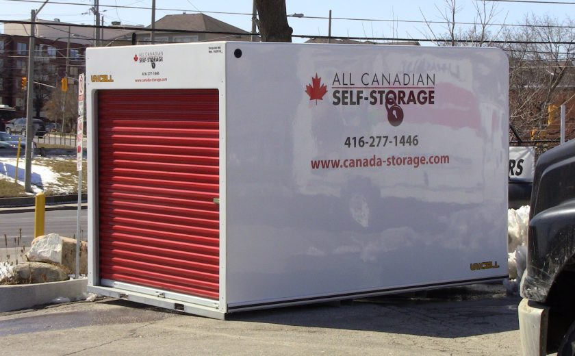 white storage unit with red door, sitting on grey pavement in parking lot, brown houses with grey roofs in the background