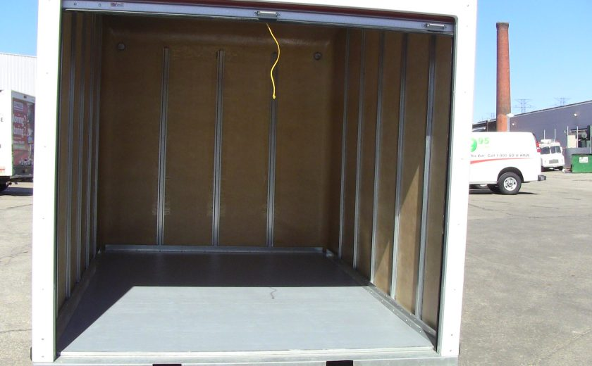 opened door white storage unit, sitting in parking lot, brown and grey inside