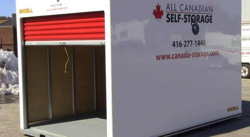 white storage unit with red door in parking lot, yellow string on door handle