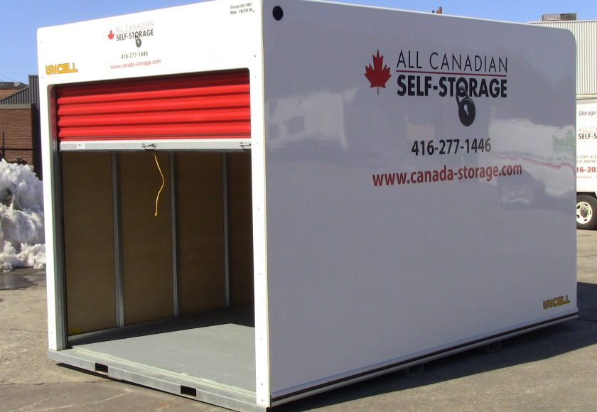 white storage unit with red door in parking lot, yellow string on door handle
