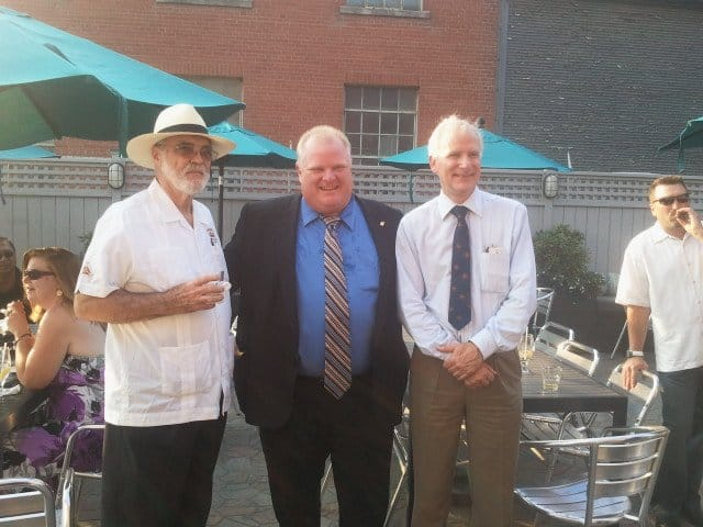 three men standing, two wearing white buttoned up shirts, the one in the middle wearing a blue dress shirt with a black blazer, grey fence in the back, teal umbrellas above the tables