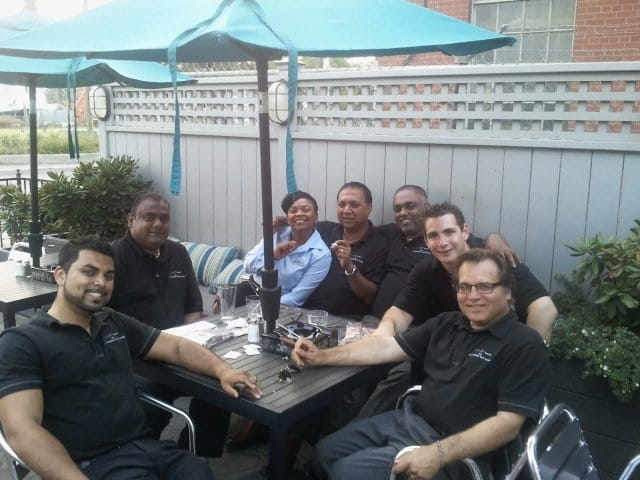 group of men wearing black gathering around black squared table, one women wearing a blue blouse, grey fence behind them, teal umbrella on top