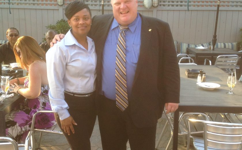 woman wearing a white blouse and black bottoms with black heels, man wearing blue dress shirt and black jacket with striped tie, black tables with silver chairs, teal patio umbrellas