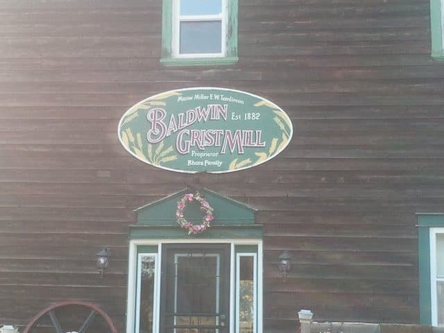brown cabin with green borders around the white windows, oval green and yellow sign, glass door below the sign