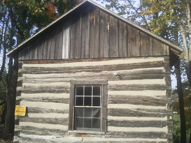 brown wooden cabin, surrounded by brown and green trees, yellow sign on the left of the cabin that says private, window in the middle