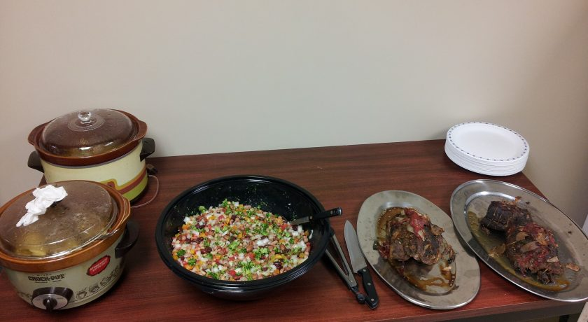 two brown and white pots, black bowl with colourful chopped vegetables, two silver plates with food on a brown table