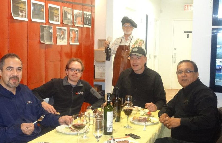 movie night, four men sitting at a rectangular table with a yellow table cloth, wine glasses and alcohol on the table, one man standing in the back holding a black bottle of wine, white and red wall