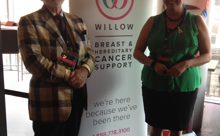 a man wearing black and yellow checkered jacket and black pants standing next to a sign that says breast and hereditary cancer support, woman wearing a green shirt and black skirt standing next to it too