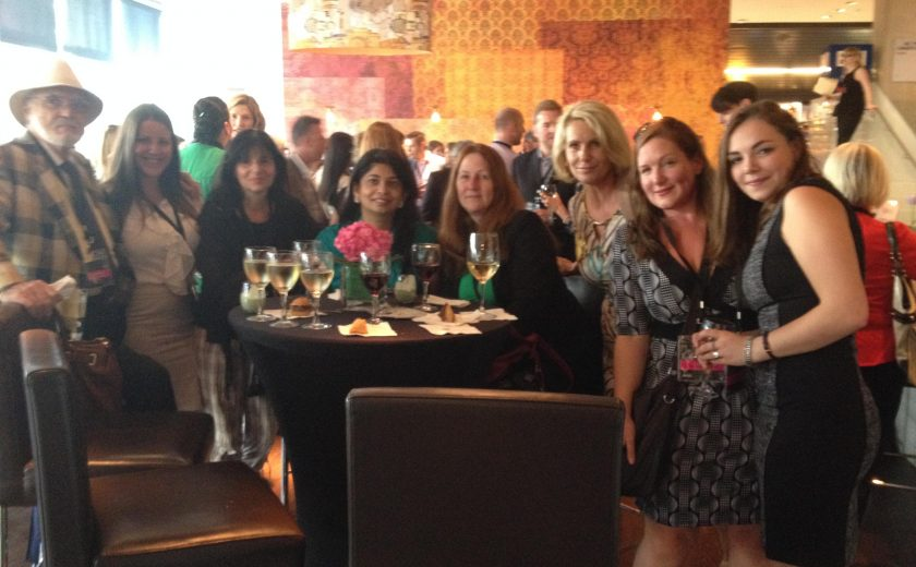 group photo eight women and one man, gathered around a black high table with black hair chairs, wine glasses on the table, red/orange/yellow wall