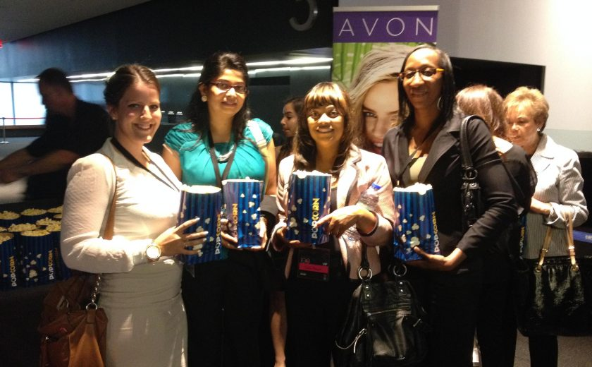 four women standing and smiling, holding blue and yellow bags of popcorn, inside a movie theatre