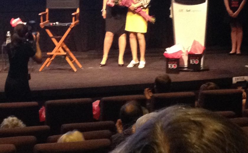 two women on stage holding a bouquet of pink flowers, woman in black taking a picture of them on stage