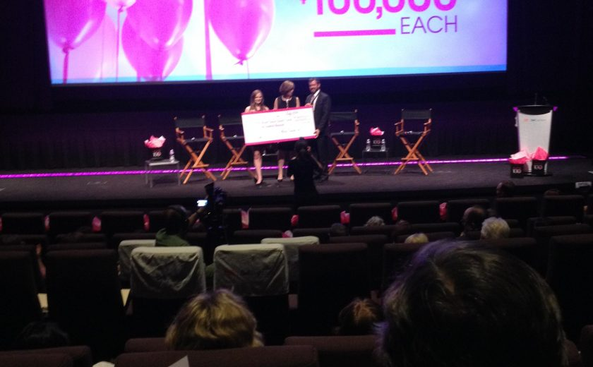 three people on a black stage holding a large cheque, pink and white balloons on the screen