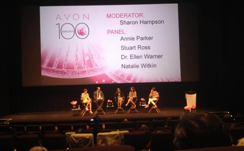 panel of five speakers sitting on brown chairs on stage, large screen with pink display