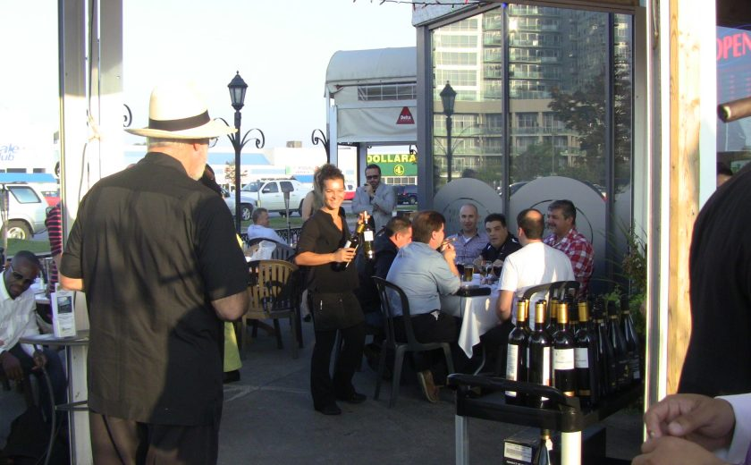 group of people sitting on the patio, cart full of black and gold alcohol bottles, parking lot filled with cars in the back, blue sky