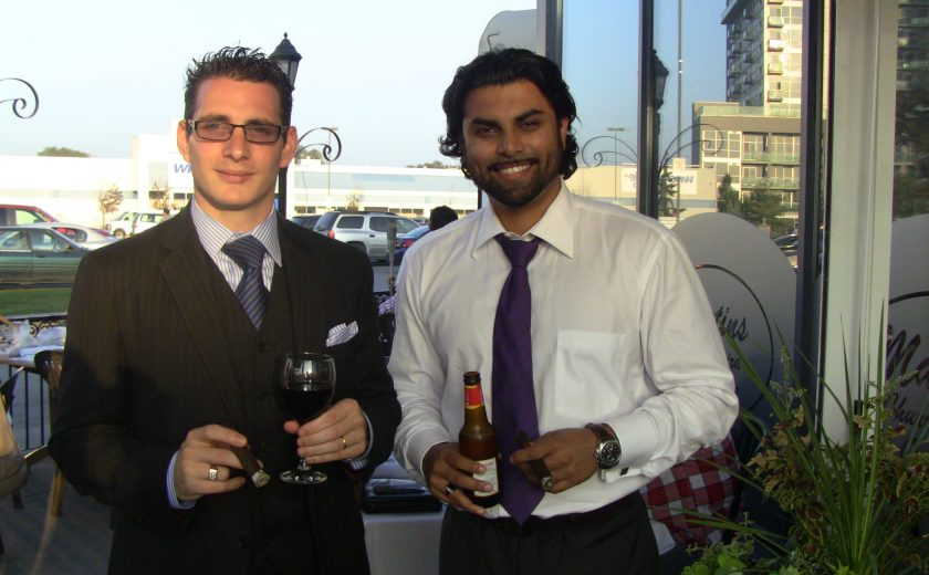 two men smiling, one man wearing a black suit, other man wearing white shirt with purple tie, both holding drinks, blue sky