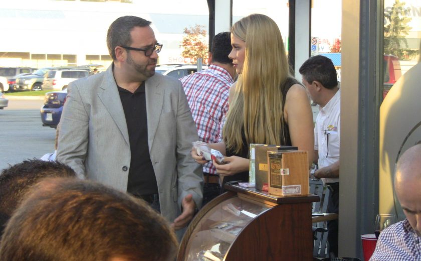 woman with long blonde hair talking to man wearing a grey suit and black dress shirt, outside on a patio