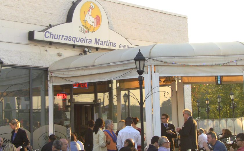 front of Churrasqueira Martins Grill House, white building with white patio tent, people sitting at tables, black gate surrounding