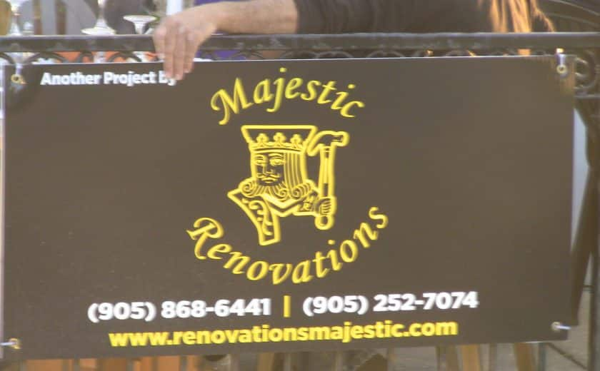 yellow, white and black majestic renovations sign hanging on black gate