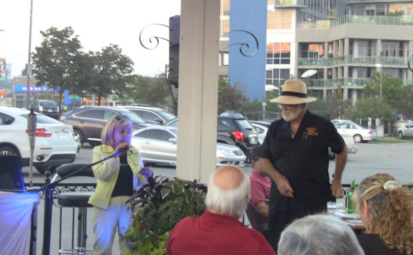 people sitting at tables listening to woman wearing a black shirt standing in front of a microphone, white pillar in the middle, buildings and parking lot in the background