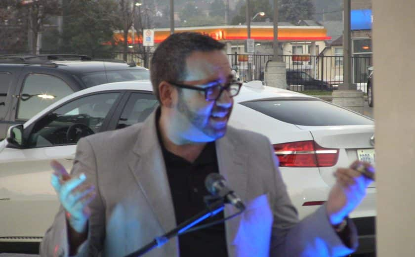 man wearing a black shirt and grey blazer talking on a black microphone, white and black car in the background
