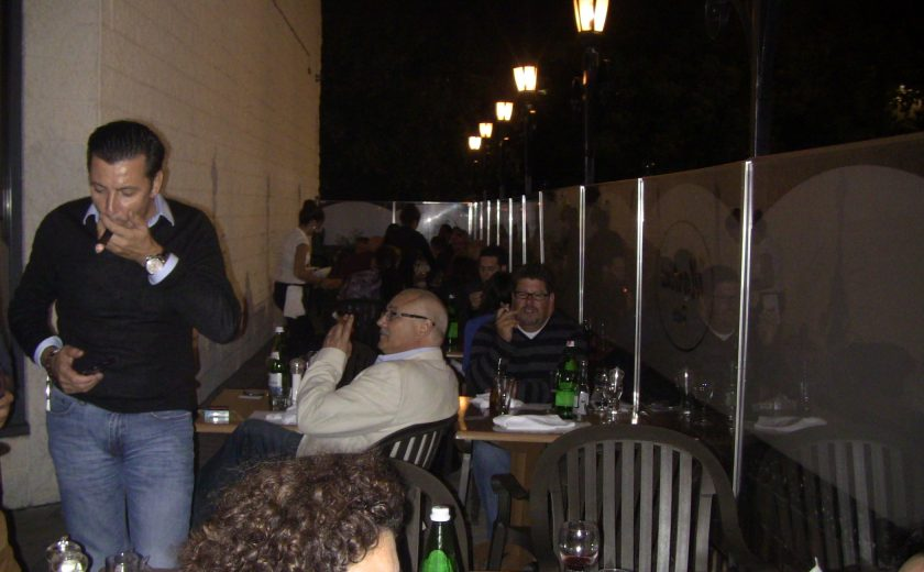 people sitting on black chairs at their brown wooden tables, patio enclosed by glass, 5 tall black lamps in the back, white brick wall on other side of glass boarders