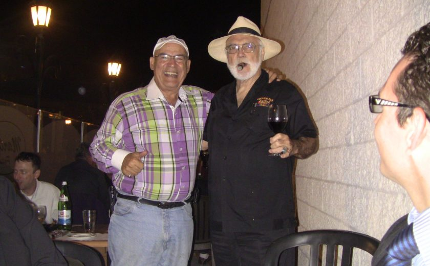 one man wearing purple and green plaid smiling with his arm around another man wearing all black with a cigar in his mouth, night sky, standing beside white brick wall