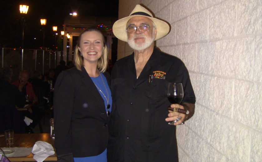 a women wearing a blue dress and black jacket standing next to a man wearing all black holding a cigar and wine glass, night sky, white brick wall on the side