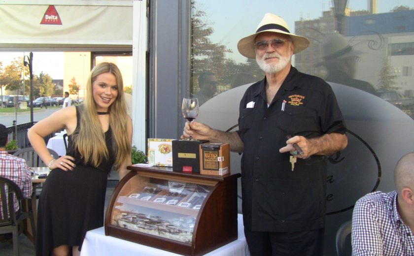 man and woman posing beside mahogany case with glass front full of cigars, case is on white table, outside