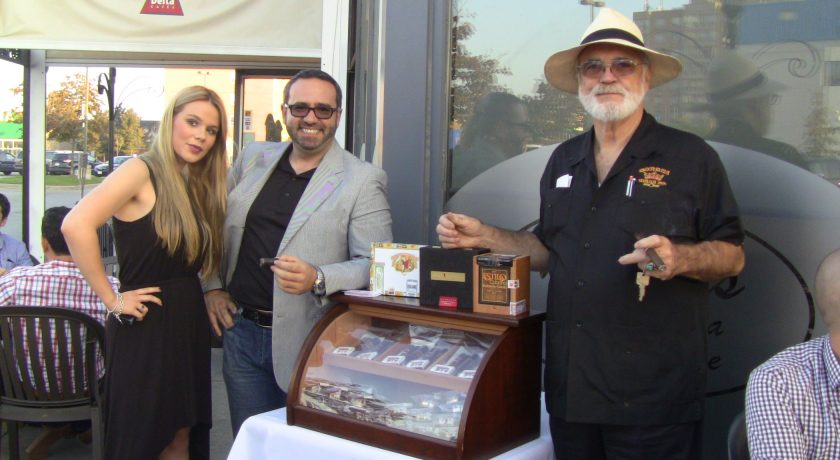 two men standing beside a mahogany case with a glass front displaying the cigars, woman standing beside the man on the left, case is on top of a white table, outside on a patio