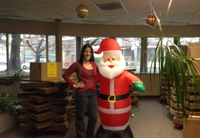 woman wearing red stripes standing beside a red and white inflatable santa, brown boxes stacked around the room, large windows, brown houses outside