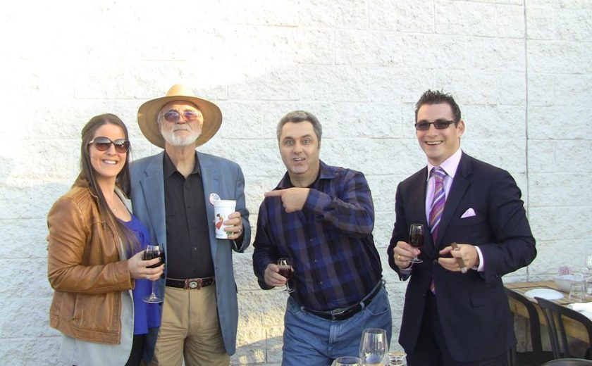 four people holding drinks standing behind a brown wooden table, white brick wall