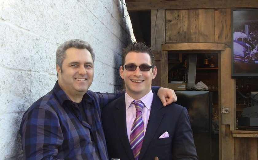 two men standing in front of a brown drink bar against a white brick wall, one man is wearing a blue plaid shirt holding a glass, other man is wearing a pink dress shirt and dark jacket holding a cigar