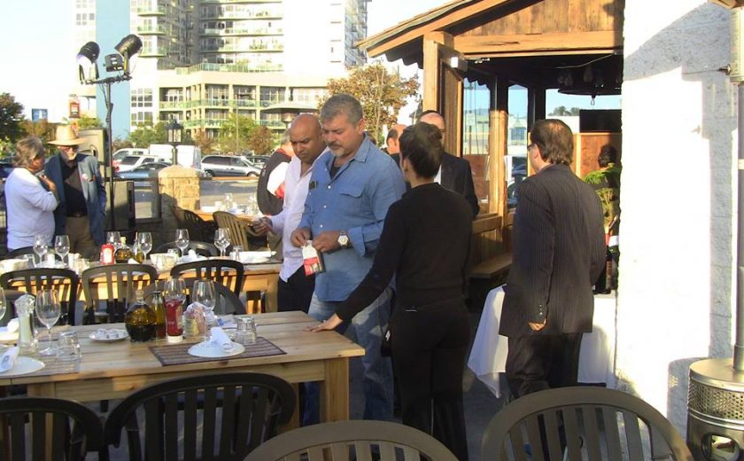 people standing around the wooden tables and black chairs on the patio of the brown and white coloured building, tall buildings and parked cars in the background