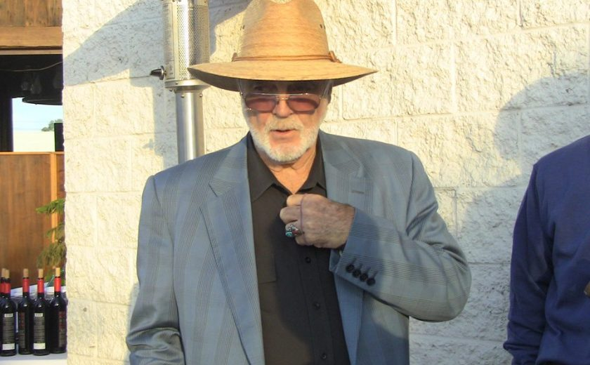 man wearing a light brown sun hat, black dress shirt, grey jacket and sunglasses against a white brick wall