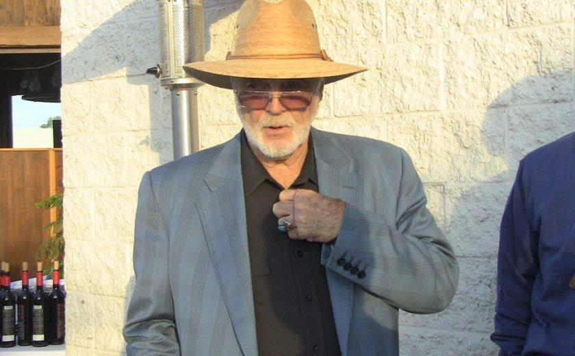 man wearing a light brown sun hat, black dress shirt, grey jacket and sunglasses against a white brick wall
