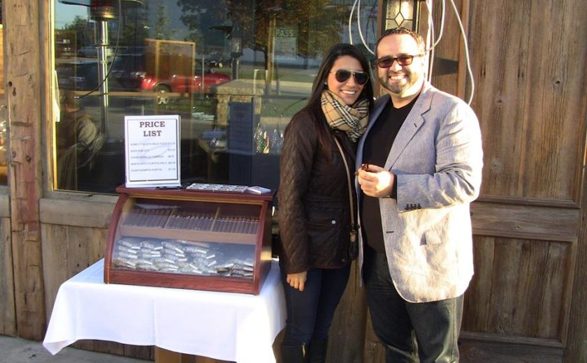 a man and a woman standing in front of a brown building with a large glass window, standing next to a mahogany case of cigars on a white square table