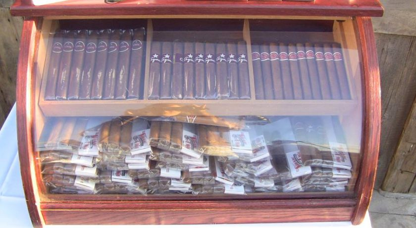 mahogany case with glass front full of packs of brown cigars sitting on a white table
