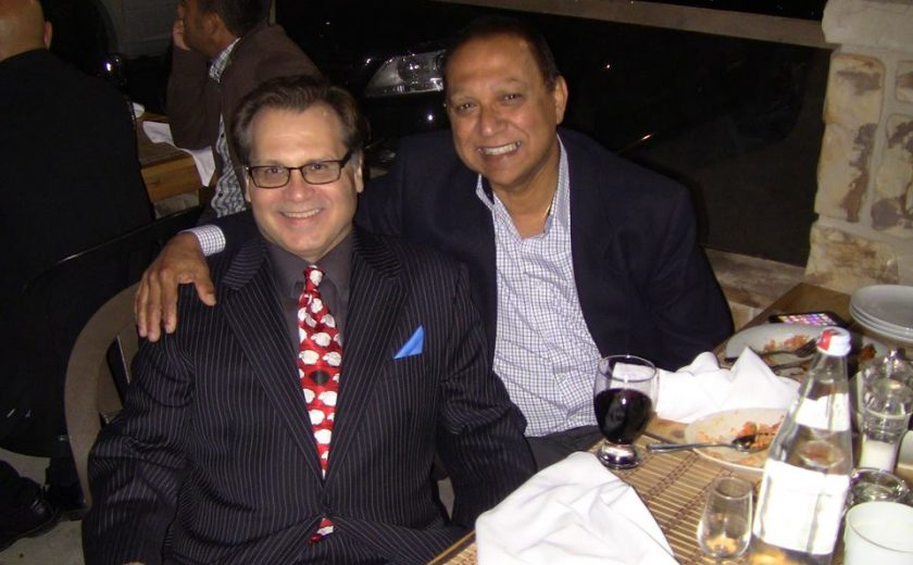 two men wearing dress shirts and jackets, one has their arm around the other, sitting at a dinner table outside with eaten food and utensils on top