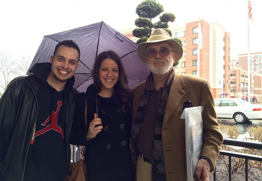 group of three smiling at camera standing, two men on the left and right side, one woman in the middle holding a purple umbrella, tall brown and beige buildings in the background